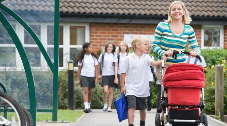 Woman with a pushchair walking her son home from school